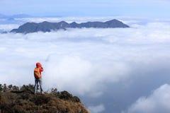 拍在山峰的妇女远足者照片 免版税库存照片