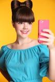 拍在巧妙的电话的愉快的微笑的滑稽的青少年的女孩Selfie照片 免版税库存图片
