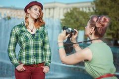 拍在影片照相机的两个美丽的行家女孩照片胜过 免版税库存照片