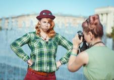拍在影片照相机的两个美丽的行家女孩照片胜过 库存图片