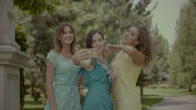 拍在手机的嬉戏的女朋友照片在公园 股票录像