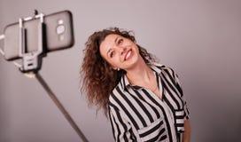 拍在智能手机的年轻女人的画象selfie照片 库存图片