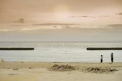 拍在海滩的人们照片与不尽的海景和日落在背景中 库存图片