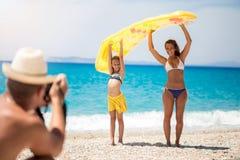 拍在海滩的愉快的家庭照片 图库摄影