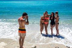 拍在海滩的青年人照片 免版税库存图片