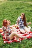 拍在电话的两个年轻愉快的女孩照片 免版税库存照片