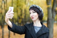 拍在电话的女孩照片在秋天城市公园、黄色叶子和树,秋季 库存图片