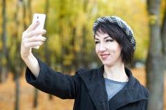 拍在电话的女孩照片在秋天城市公园、黄色叶子和树,秋季 库存照片