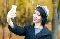 拍在电话的女孩照片在秋天城市公园、黄色叶子和树,秋季 图库摄影