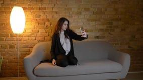 拍在电话的年轻俏丽的白种人深色的女性特写镜头射击照片坐长沙发户内在a 库存照片