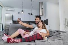 拍在细胞巧妙的电话的愉快的微笑的夫妇Selfie照片坐在现代公寓、年轻人和妇女的长沙发 免版税库存照片