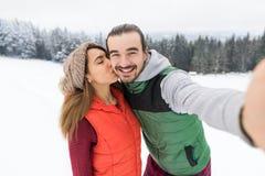 拍在聪明的电话斯诺伊村庄木乡间别墅人妇女冬天雪的夫妇Selfie照片 库存图片