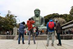 拍在镰仓的了不起的菩萨的前面游人照片, 免版税图库摄影