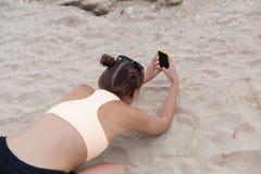 拍在yhe膝盖的美丽的妇女照片与聪明的电话技术天堂海滩目的地夏天旅行癖假期 库存照片