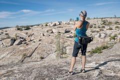 拍坚固性风景的照片妇女徒步旅行者 免版税库存图片