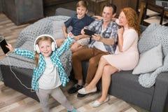 拍女儿听的音乐,愉快的微笑的家庭的照片在耳机的父亲坐长沙发在客厅 图库摄影