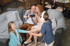 拍女儿和儿子听的舞蹈音乐,愉快的微笑的家庭的照片在耳机的父亲坐长沙发  免版税库存照片