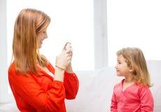 拍女儿的照片微笑的母亲 图库摄影