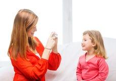 拍女儿的照片微笑的母亲 库存照片