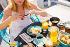 拍她的与手机的早餐的照片妇女 库存照片