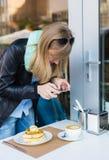 拍她的咖啡店早餐的照片妇女 库存图片