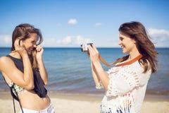 拍她的海滩的朋友的照片愉快的妇女 图库摄影