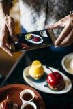 拍她的食物的照片妇女 免版税库存照片