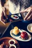 拍她的食物的照片妇女 库存照片