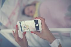 拍她睡觉的婴孩的照片年轻母亲 免版税库存照片