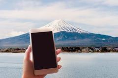 拍富士山的照片有一个巧妙的电话的妇女 免版税库存照片