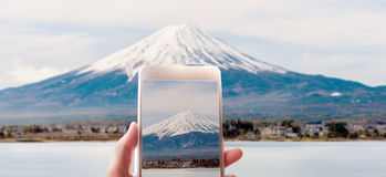 拍富士山的照片有一个巧妙的电话的妇女 免版税图库摄影