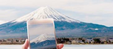 拍富士山的照片有一个聪明的响度单位的妇女的手 库存图片