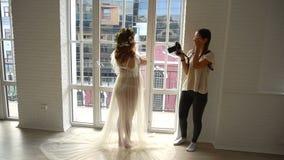 拍怀孕的少妇的照片摄影师站立在大窗口附近 影视素材