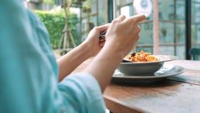 拍意粉食物的照片在智能手机的一个少妇,拍摄与流动照相机的膳食 影视素材