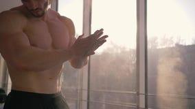 拍手与白色白垩粉末的强的运动员胳膊在准备在健身房的训练锻炼期间在慢动作 影视素材