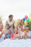 拍手为小女孩生日的快乐的大家庭 免版税图库摄影