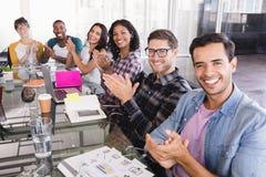 拍手企业队的画象,当坐在创造性的办公室时 免版税库存照片