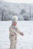 拍手和微笑在雪的小女孩 免版税库存照片