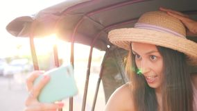 拍手机在自行车人力车出租汽车的年轻旅游妇女Selfie照片有惊人的透镜火光日落作用的  股票录像