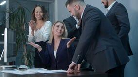 拍手的商人庆祝成功在一次会议上在办公室 免版税库存照片