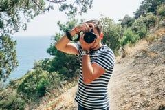 拍摄一台专业照相机的摄影师男性游人 免版税库存照片
