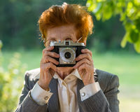 拍摄一台影片照相机的年龄的妇女在公园 免版税库存照片