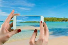 拍摄与一台聪明的电话照相机的后面观点的妇女照片在海滩的天际 免版税库存图片