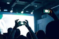 拍摄与巧妙的电话的人们照片在音乐音乐会期间 夺取在一个手机的人录影在音乐节 免版税图库摄影