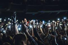 拍摄与巧妙的电话的人们照片在音乐音乐会期间 夺取在一个手机的人录影在音乐节 免版税库存图片