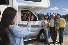 拍摄与手机的十几岁的女儿家庭在RV之外在湖 免版税库存照片