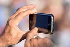 拍摄与手机的手 库存图片