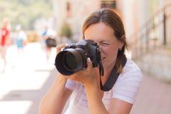 拍摄与数字式照片照相机的年轻美丽的旅游妇女照片 旅行癖概念 免版税图库摄影