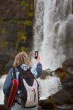 拍摄与智能手机waterfa的女性资深旅客 免版税库存照片