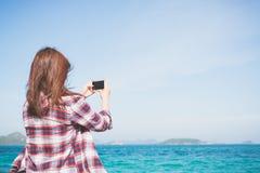 拍摄与聪明的电话照相机的后面观点的妇女照片在海滩的天际 免版税库存照片